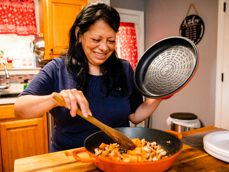 Alice Chapa cooking in the kitchen after her colorectal cancer treatment