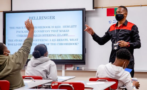 Robert Gillums after his pancreatic cancer treatment teaching in the classroom, one student raising their hand