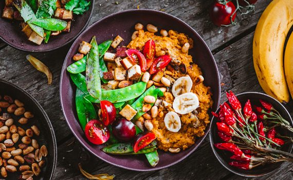 Vegan meal with vegetables, tofu, and healthy foods in a black bowl